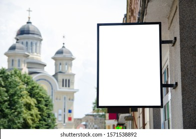 Blank vertical board outside on a building facade wall with big city church and urban view in the background. Empty white advertising placard outdoors with copy space for your text, image or design