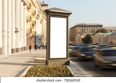 Blank vertical street advertising pillar with city background.