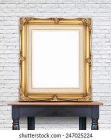 Blank vintage golden photo frame lean at white brick  wall on wood table,Template Mock up for add picture.