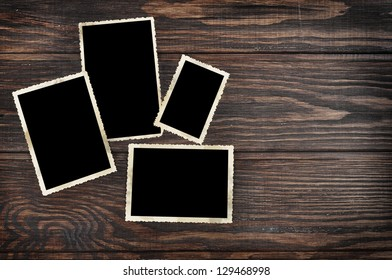 Blank vintage photo frames on old wooden background. Clipping path included.