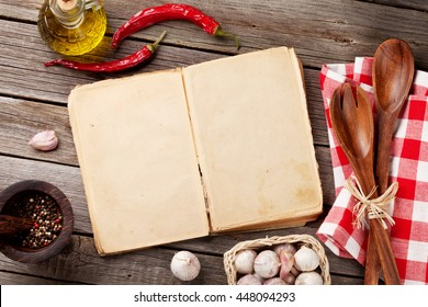 Blank vintage recipe cooking book, utensils and ingredients on wooden table. Top view with copy space