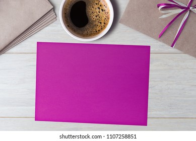 Blank violet card with envelopes and coffee cup on wooden table.