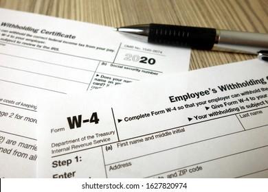Blank W-4 tax form and a pen. Tax season