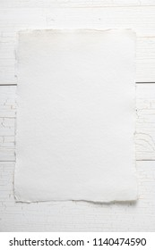 Blank watercolor paper on white wooden background, rough texture, copy space, template