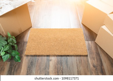 Blank Welcome Mat, Moving Boxes and Plant on Hard Wood Floors.