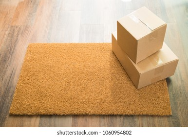 Blank Welcome Mat On Wood Floor With Shipment of Boxes.