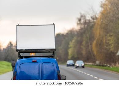 Blank white advertising banner sign on car roof next to UK motorway