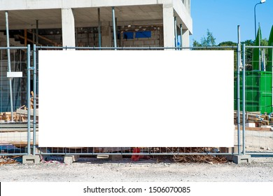 Blank white banner for advertisement mounted on the fence of construction site on a sunny day.