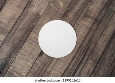 Blank white beer coaster on wooden background. Responsive design mockup. Flat lay.