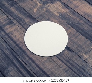 Blank white beer coaster on wooden background.