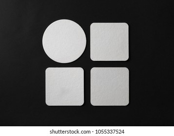 Blank white beer coasters on black paper background. Responsive design mockup. Flat lay.