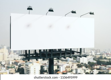 Blank white billboard on bright city background. Retail, advertisement and commerce concept. Mock up, 3D Rendering