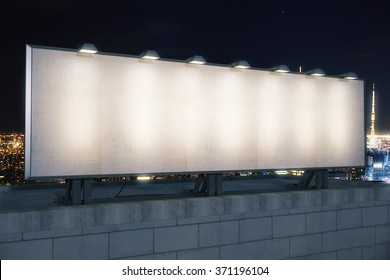 Blank white billboard on the top of building at night city background, mock up
