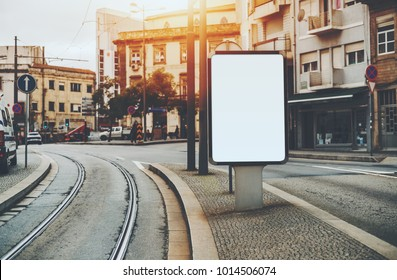 Blank white billboard placeholder mockup on city street between road and tram-line; empty banner template in urban settings on pavement stone sidewalk with facades of residential houses around