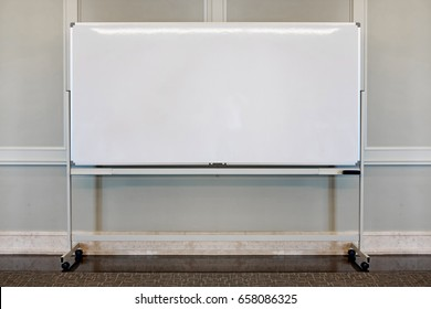 A blank white board stand against a wall.