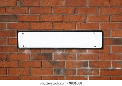 Blank white British street sign on a red brick wall.