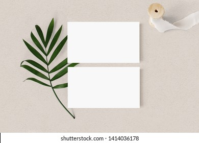 Blank white business cards mockups with palm leaf and silk ribbon on textured table backgound. Elegant modern template for branding identity. Tropical design. Wedding stationery. Flat lay, top view.