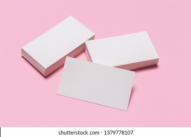 Blank white business cards on pink background. Mockup for branding identity. Template for graphic designers portfolios. Top view.