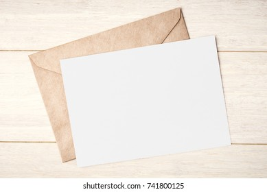 Blank white card and envelope on wooden table
