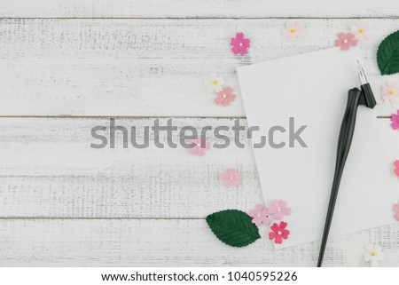 8e2137de647 Blank white card and oblique pen decorate with pink paper flowers and green  leaves on white