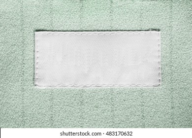 Blank white clothes label on green cloth as a background