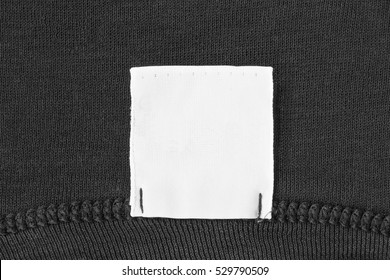 Blank white clothes label on black cloth as a background