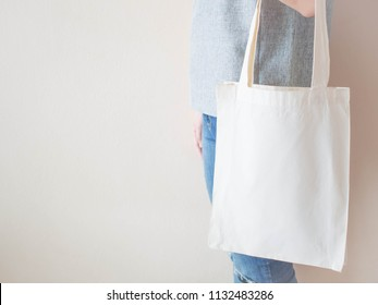 Blank white cotton tote bag with handle mock up design. Close up of woman holding eco or reusable shopping bag. No plastic bag and ecology concept. Copy space.