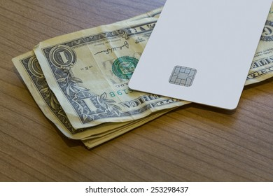 A Blank white Credit or Debit Card and a couple of dollar notes on a wooden table