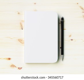 Blank white diary cover with pen on wooden table, mock up