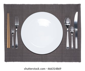 Blank white dish, fork, spoon, knife and chopsticks on fabric mat background.