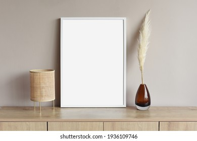 Blank white empty picture frame mockup on grey wall. Copy space. Artwork showcase. View of modern scandinavian style interior with chair. Home staging and minimalism concept
