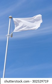 Blank white flying flag on a blue sky - Shutterstock ID 302529719