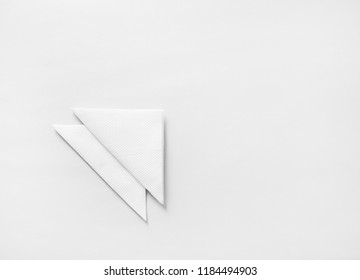 Blank white folded napkins on paper background with copy space. Flat lay.