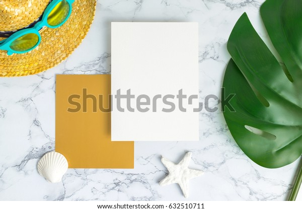 Blank white and gold paper card on marble table top view with summer beach accessories and shell,starfish,tropical palm leaves ,Summer vacation concept,Mock up template for adding your design or text