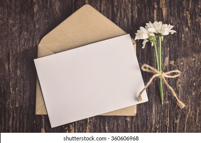 Blank white greeting card with brown envelope and wither Mum flowers on wooden table with vintage and vignette tone