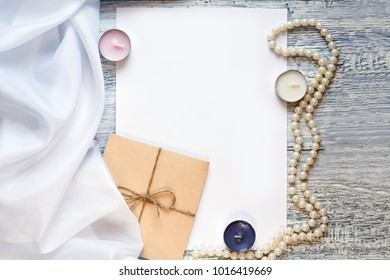 blank white greeting card and envelope with candles,beads over rustic table with copy space. mock up.