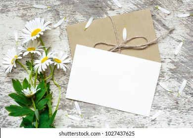 blank white greeting card and envelope with white chamomile flowers over rustic wooden background. mock up. flat lay