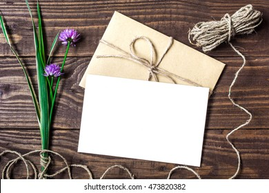 Blank white greeting card and envelope with purple wildflowers and on brown rustic wood background for creative work design