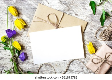 Blank white greeting card and envelope with yellow wildflowers and gift box on white rustic wood background for creative work design. flat lay