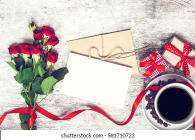 blank white greeting card and envelope with coffee cup and red roses flowers with gift boxes over rustic table. mock up. vintage toning