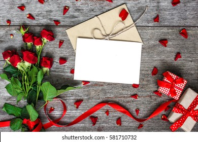 blank white greeting card and envelope with red roses flowers and red ribbon with gift boxes over rustic table. mock up. valentines day background