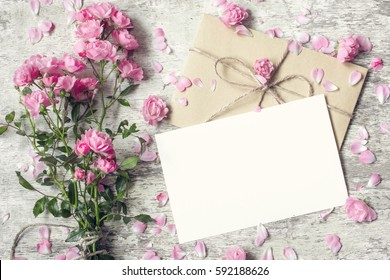Blank white greeting card and envelope with pink rose flowers mock up on white rustic wood background for creative work design. top view