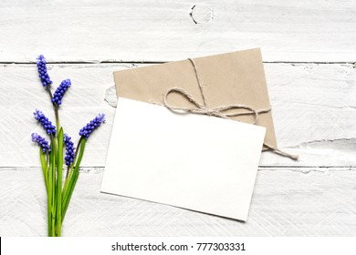 blank white greeting card and envelope with spring blue flowers bouquet over white wooden background. top view. mock up