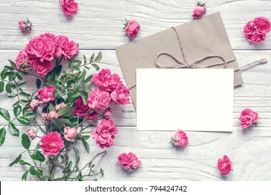 blank white greeting card and envelope with pink rose flowers bouquet on white wooden table. mock up. top view. valentines day background. vintage toning