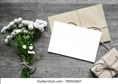 blank white greeting card with white flowers bouquet and envelope with gift box on rustic wooden background .top view. mock up