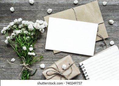 blank white greeting card with white flowers bouquet and envelope with gift box and paper notebook on rustic wooden background .top view. mock up