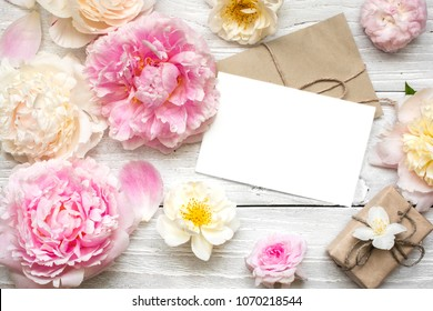 blank white greeting card in frame made of peony and roses flowers and envelope with gift box on white wooden background. flat lay. top view. mock up