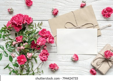 blank white greeting card and gift box with pink rose flowers bouquet on white wooden table. mock up. top view. valentines day background. vintage toning