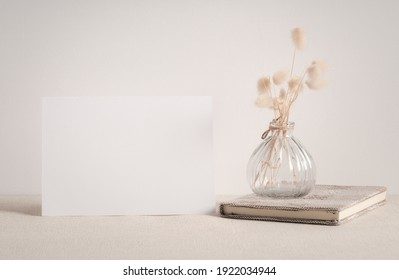 Blank white greeting card mock up.decoration with dried Lagurus ovatus flowers composition in modern glass vase and craft book  on  beige table and cement wall background
