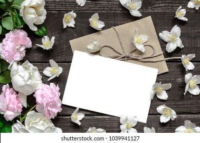 blank white greeting card with pink and white roses in frame made of jasmine flowers over rustic wooden table. flat lay. top view